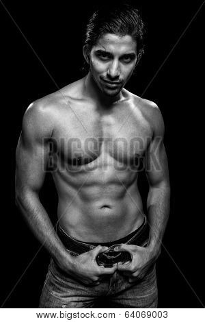 Athletic man, shirtless. Studio shot over black.