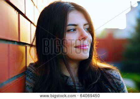 Portrait of a thoughtful woman near brick wall