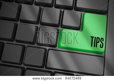The word tips on black keyboard with green key