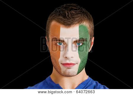 Composite image of serious young ivory coast fan with facepaint against black