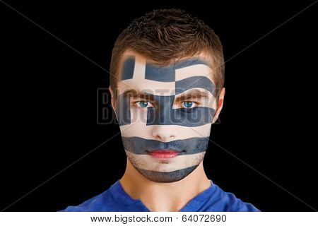 Composite image of serious young greece fan with facepaint against black