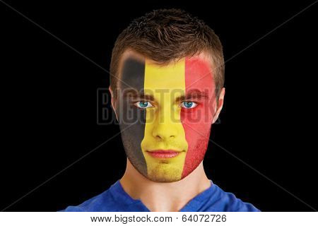 Composite image of serious young beligan fan with facepaint against black