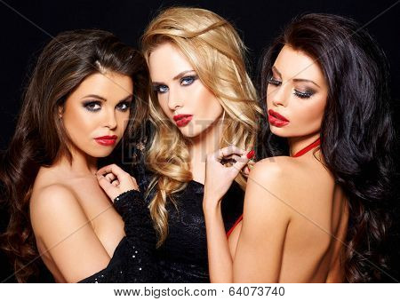 Trio of elegant beautiful coquettish women in evening wear posing together flirting with the camera giving seductive sensual looks