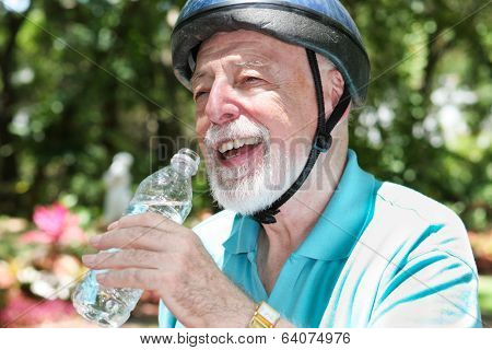 Active senior man wearing a bicycle helmet stops to drink bottled water.