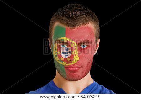 Composite image of serious young portugal fan with facepaint against black