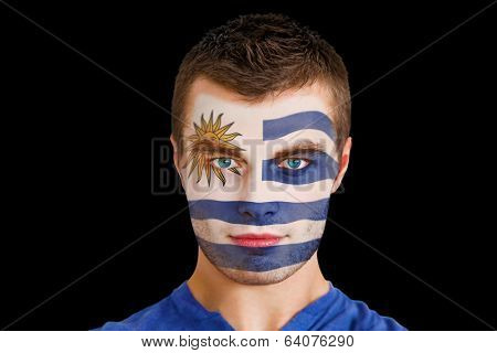 Composite image of serious young uruguay fan with facepaint against black
