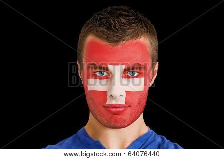 Composite image of serious young swiss fan with facepaint against black