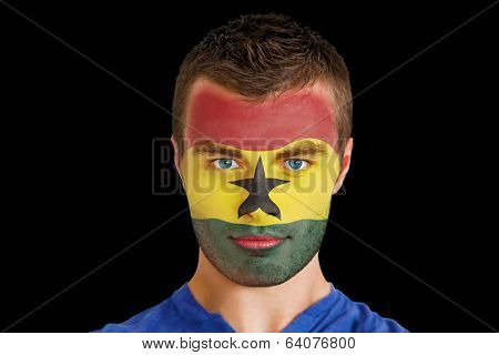 Composite image of serious young ghana fan with facepaint against black