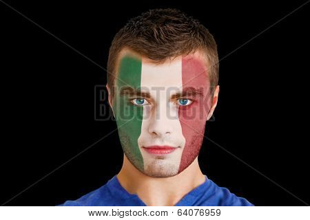 Composite image of serious young italy fan with facepaint against black