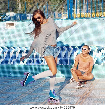Two Beautiful Young Girls In Sunglasses In An Empty Pool
