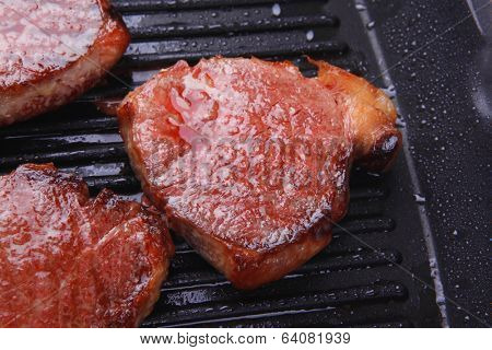roast bloody beef fillet steaks on black teflon grill plate isolated on white background