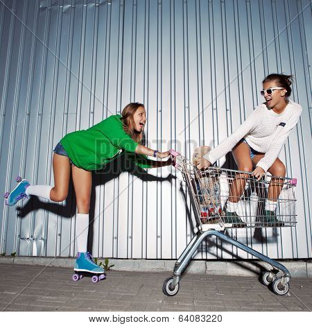 Two Beautiful Young Girls With A Skateboard, Roller Skates And A Supermarket Trolley