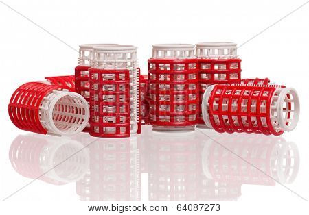 Stack of red hair curlers isolated on white background