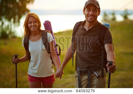 Portrait of couple of happy hikers going in the countryside