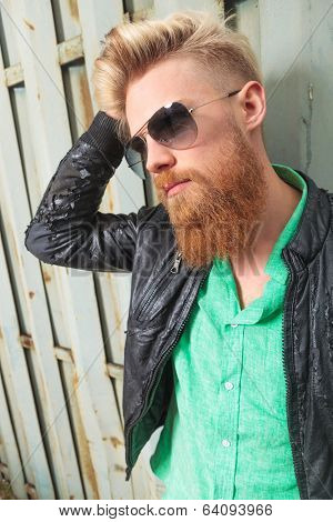 close up portrait of a young casual redhead bearded man with his hand in his hair, looking away from the camera