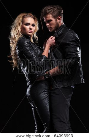 young blonde woman pulling her boyfriend by his jacket's collars while looking into the camera; he is holding her by the hips and looking at her . on black background