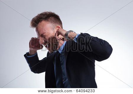young business man plugging his ears with his fingers and closing his eyes while screaming. on a light gray studio background