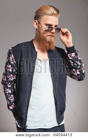 casual young man with a long red beard taking off his sunglasses and looking away from the camera. on gray studio background