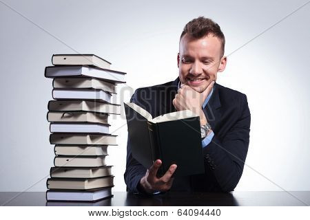 young business man sitting at his office with a stack of books and reading with a smile on his face while holding his hand on his chin. on a light studio background