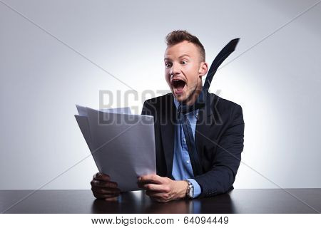 young business man sitting at the desk and reading some breaking news with amazemend and with his tie in the air. on a light gray studio backgroud