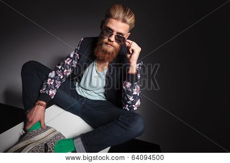 young bearded man sitting in the studio and taking off his sunglasses while looking into the camera. on a black studio background