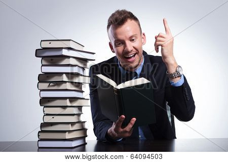 young business man reading at an office with a stack of books and pointing up with a smile on his face, as he understands the idea. on a light studio background