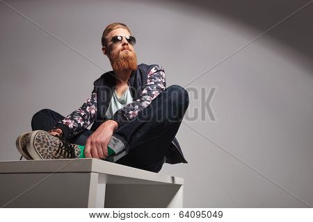casual young man with a long red beard sitting on a table with his hands on his feet and looking away from the camera. in a gray background studio