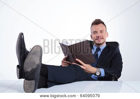 young business man with his feet on the desk smiling for the camera while holding an open book in his hands. on a light studio background
