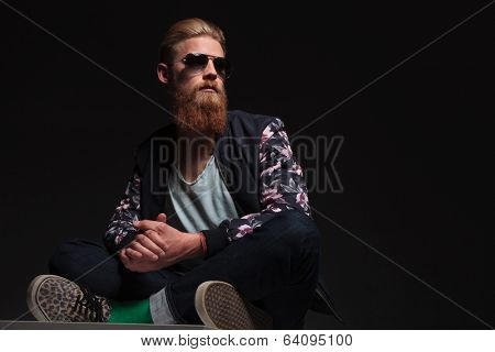 seated young bearded man looking away with his feet crossed and his palms together. on a black studio background