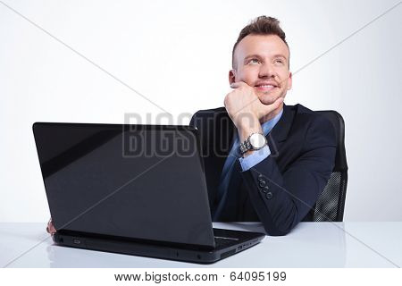 young business man looking up while sitting at his laptop with his hand on his chin and smiling. on a gray studio background