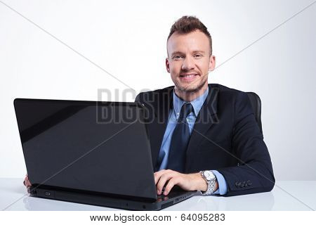 young business man sitting in front of his laptop and looking into the camera with a smile on his face . on a gray studio background