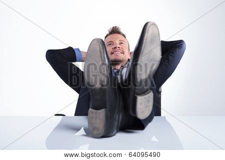 young business man holding his feet on the desk and his hands behind his head while smiling away from the camera. on a light gray studio background