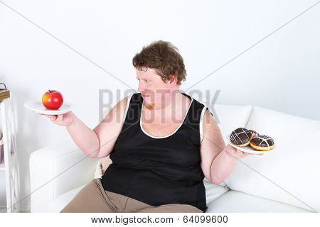 Fat man holding plated with apple and donuts on home interior background.  Choosing between good healthy food and bad unhealthy food
