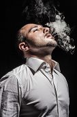 foto of underworld  - a young man in a white shirt smoking a cigarette over black background - JPG