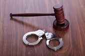 stock photo of lockups  - Photo Of Gavel And Handcuffs On Wooden Table - JPG