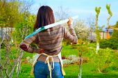 stock photo of ordinary woman  - Back view portrait of a woman with shovel in garden - JPG
