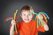 stock photo of licorice  - Young boy holding colorful licorice candy - JPG