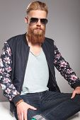 picture of straight jacket  - casual young man with a long red beard sitting with a leg over the other while looking straight into your eyes - JPG