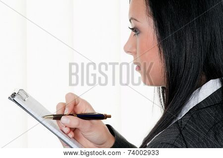 manager with clipboard in controlling takes notes