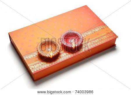 An indian sweet box with two lamps placed on it.