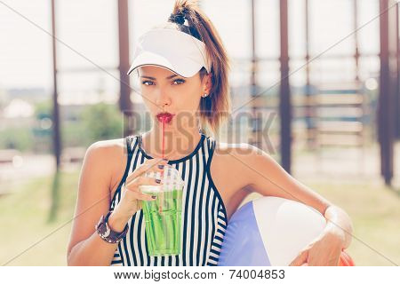 Sporty Woman Drinking Water Against The Sports Ground