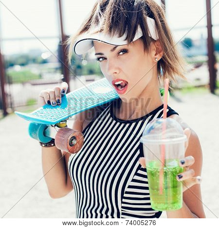 Sporty Woman With Skateboard Drinking Water Against The Sportsground