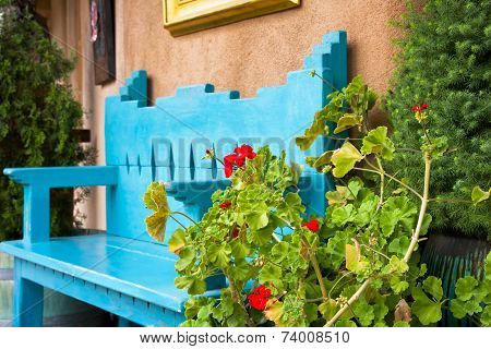Red Flowers In Front Of An Antique Bench