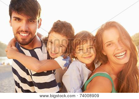 Parents Giving Children Piggybacks On Summer Holiday