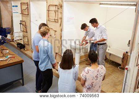 College Students Studying Plumbing Working On Washbasin