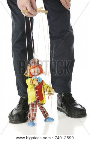 A clown marionette performing between the legs and under the hand of a puppet master.  Isolated on white.