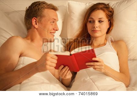 Close-up Of Couple Reading Book