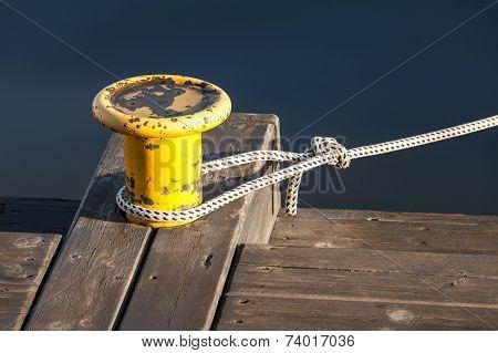 Yellow Mooring Bollard With Nautical Rope On Pier