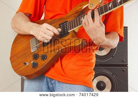 Hands of man put guitar chords