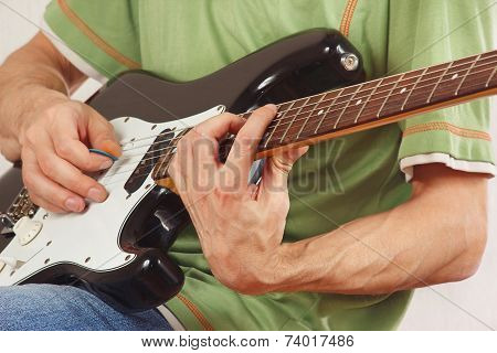 Musician put fingers for chords on electric guitar